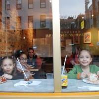 窓越しにピザを食べる少女たち - 岡田光世
